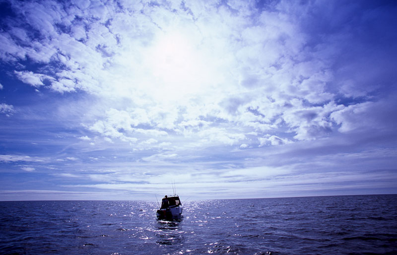 a small boat far out at sea