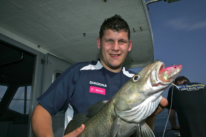 an angler with a cod taken on a pink shad