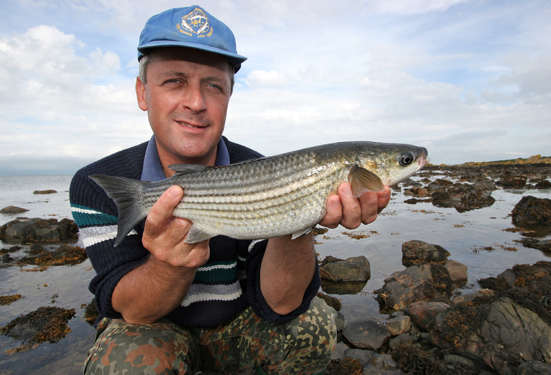 Steve Walker holds a thick lipped grey mullet