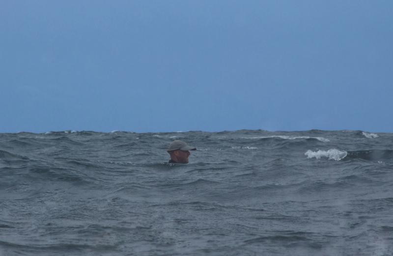 a kayak angler barely visbale above the swell