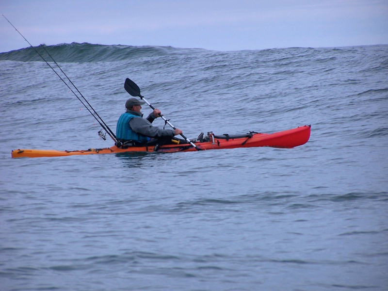 a kayak angler padding at sea