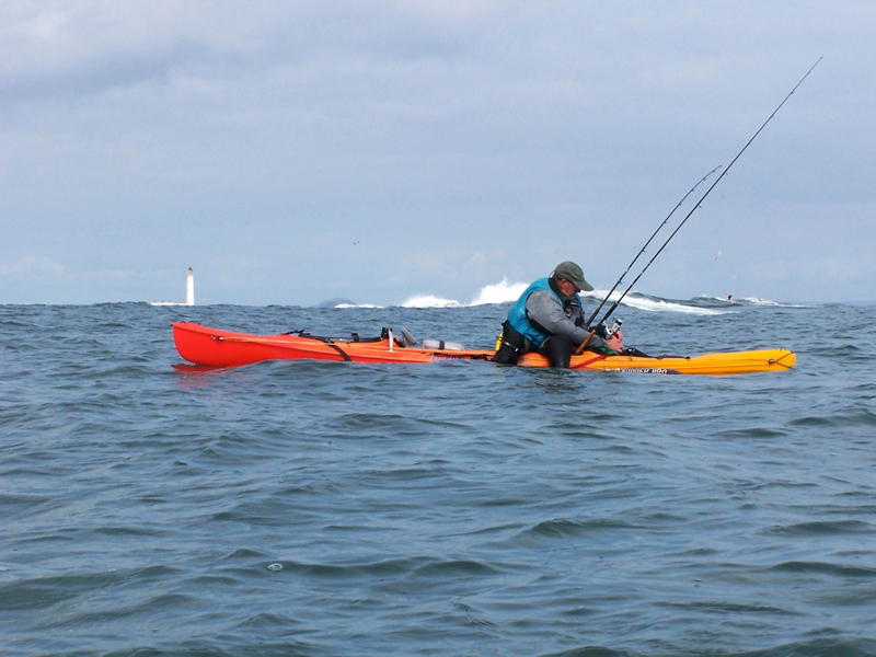 a kayak angler sorting his tackle at sea with waves cresting