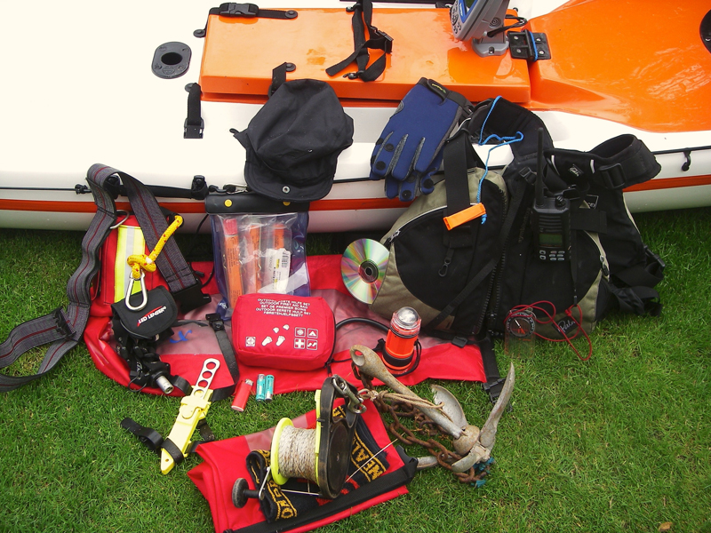 all the gear required layed out beside a kayak