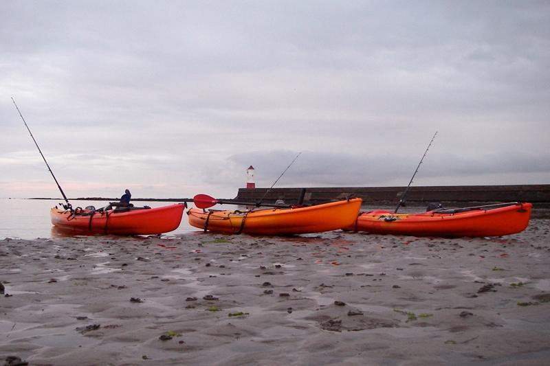 three orange kayaks lying on a beach