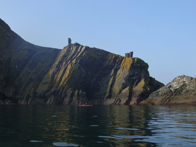 a ayak angler dwarfed by sea cliffs