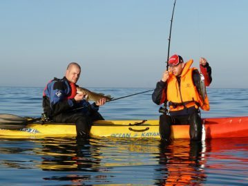 two anglers on a kayak with fish