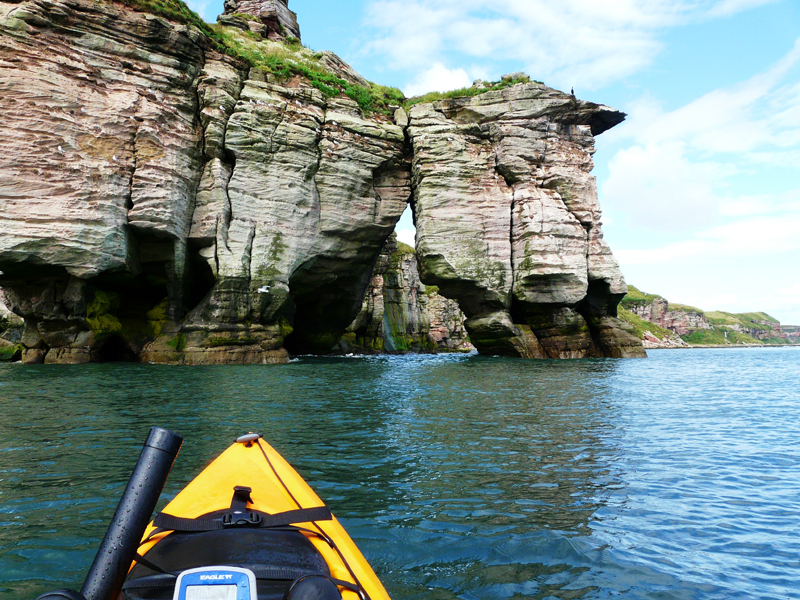 the bows of a kayak approaching a coastal arch
