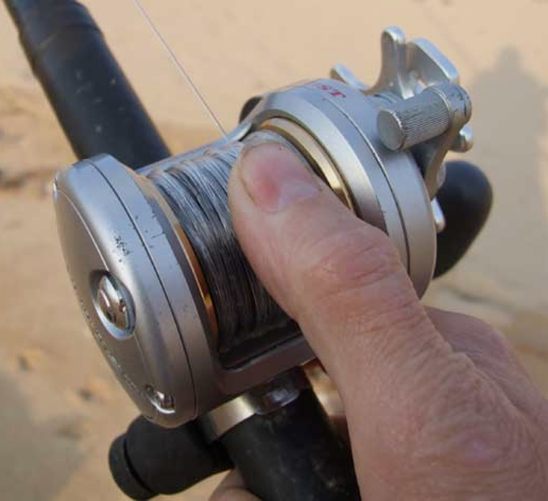 close up of an anglers thumb on the diawa saltist 20H