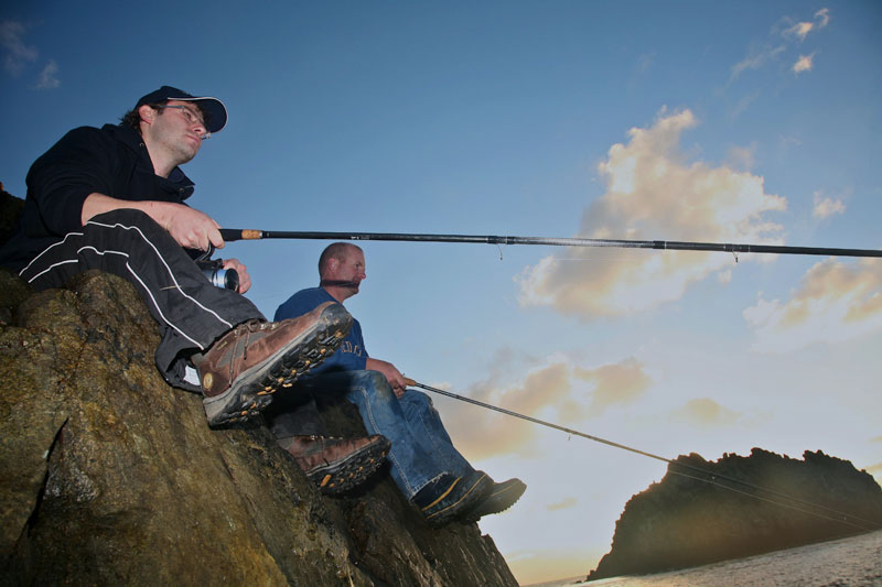 two angler wait patiently sitting on the rocks