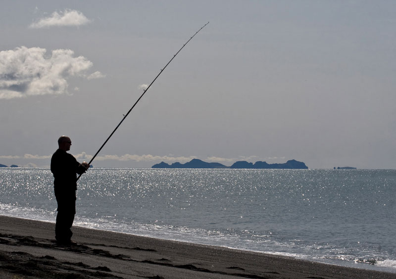 angler standing on a black beach in Iceland