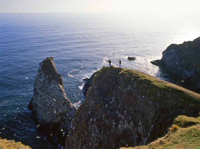 two angler perched on high rocks at St Abbs Head
