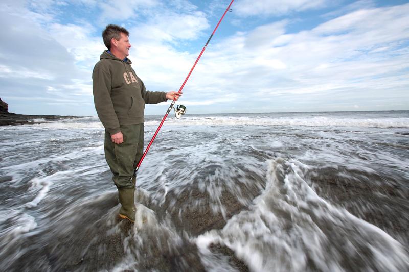 an angler with a long rod on rocks