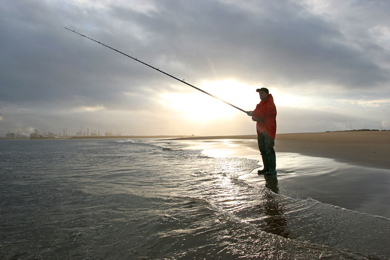 an angler on the Tees shore at sunset