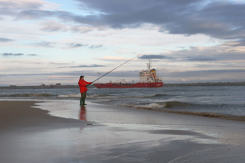 an angler in red fishing as ship passes