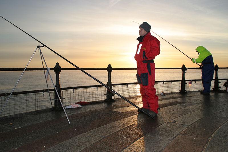 two anglers on Roker pier Sunderland at sunrise