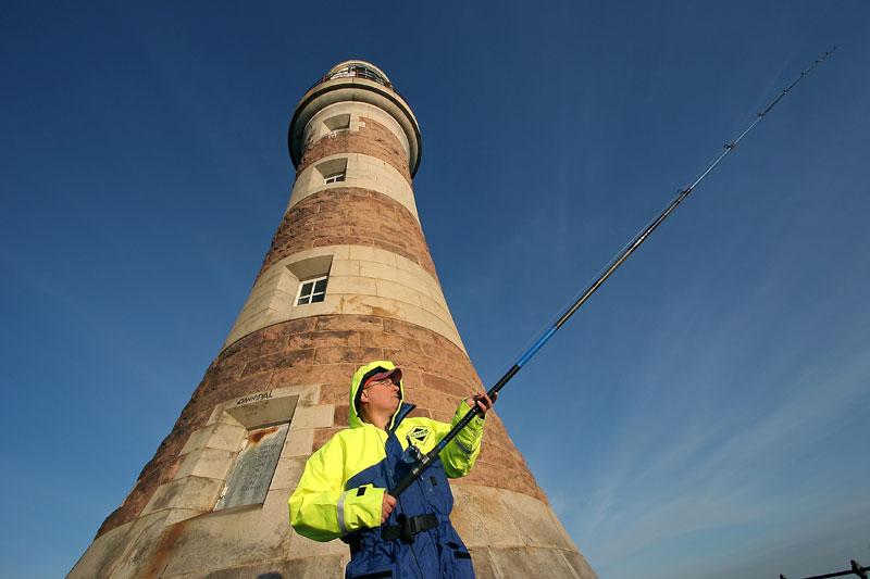 an angler beside the Roker pier lighthouse