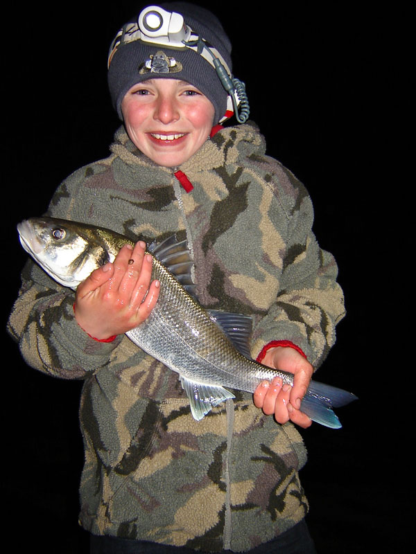 a smiling young angler with a bass