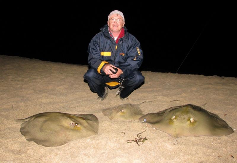 an angler on a Sardinian beach with three stingrays