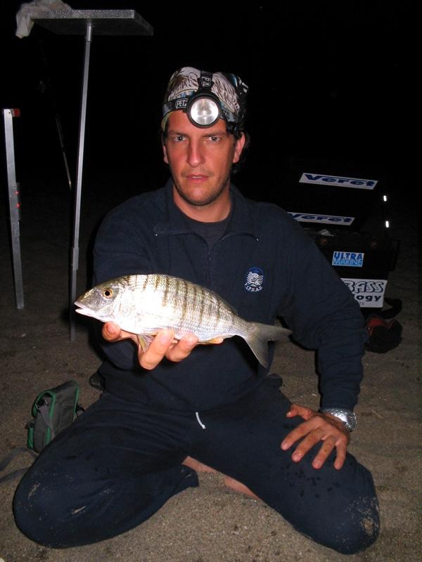 an angler displays a fish from Sardinia at night