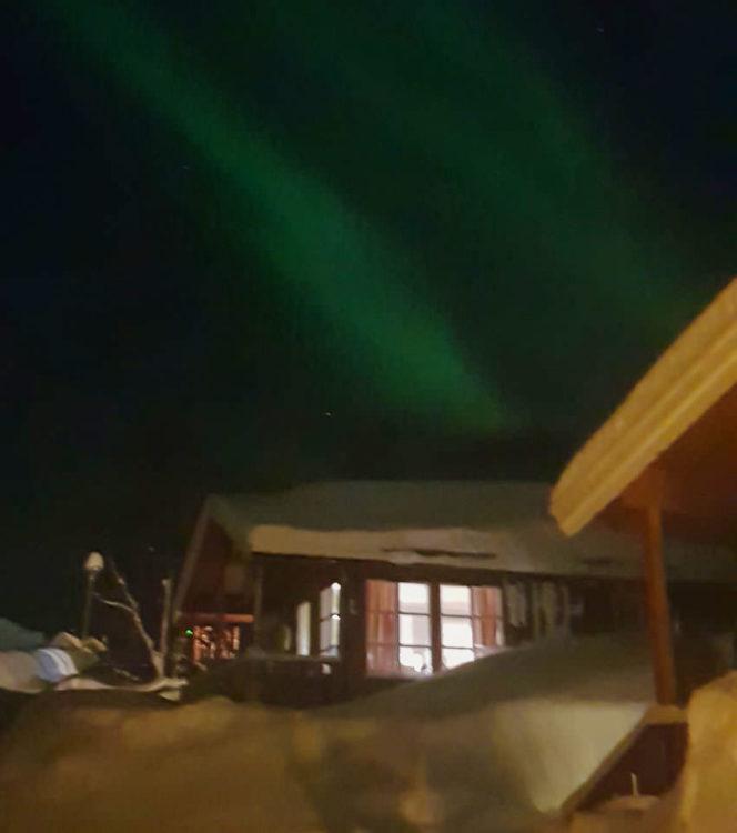 Northen lights over the wooden cabin