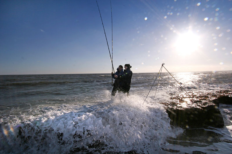 Two anglers stand in the breaking waves